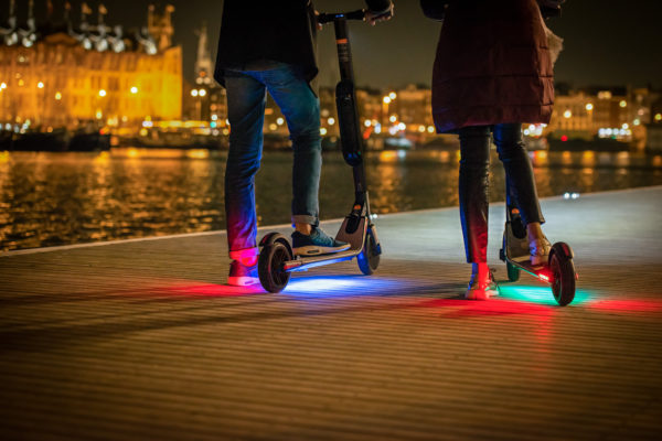 Ninebot Segway ES4 electric scooter on a promenade with friend and underside lights on