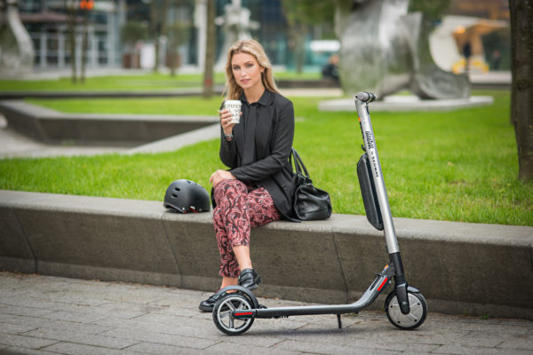 Ninebot Segway ES4 electric scooter standing up next to lady sitting down drinking coffee