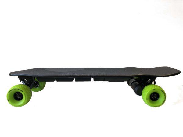 slick revolution urban kick electric skateboard with green rough stuff wheels in a side profile