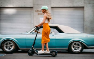 Boosted REV electric scooter ridden by a lady through town
