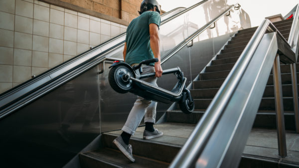 Boosted REV electric scooter carrying up stairs